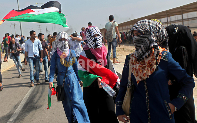 Palestinian girls gather during clashes with Israeli security forces next to the border fence with Israel, at the Erez crossing in the northern Gaza strip, on October 13, 2015. A wave of stabbings that hit Israel, Jerusalem and the West Bank this month along with violent protests in annexed east Jerusalem and the occupied West Bank, has led to warnings that a full-scale Palestinian uprising, or third intifada, could erupt. The unrest has also spread to the Gaza Strip, with clashes along the border in recent days leaving nine Palestinians dead from Israeli fire. Photo by Ashraf Amra