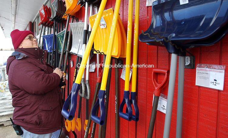 WATERBURY CT. 25 January 2017-012517SV06-John Giudice arranges snow shovels outside Schmidt's &amp; Serafines True Value Hardware in Waterbury Wednesday. Weeks of 50-degree days and snow days far and few between has made for a harsh winter for the businesses that depend on it to sell shovels, snow blowers and ice melt, as well as home heating businesses. Area merchants are hoping for a frigid, snowy February. <br /> Steven Valenti Republican-American