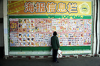 A woman looks at a listing of sales items outside the Auchan supermarket in Nanjing, China.