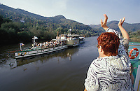 """A passenger of the Katharina von Bora waves hello to the over 100 years old paddle wheeler MS Pirna of Dresden's """"White Fleet"""", on the Elbe near Decin."""