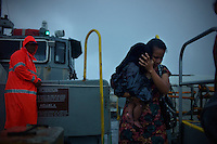 A Marshallese woman and child disembark from a ferry boat which carries workers between the U.S. Army base on Kwajalein to Ebeye, Marshall Islands on June 18, 2012. Over 12,000 people live on the tiny overcrowded island of 36 hectares. Strict rules mean that only authorized workers or Marshallese with special permission are allowed to visit the U.S. base.