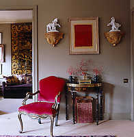 "In the living room ""Mouse"" grey walls set off a gilt-framed painting and an armchair upholstered in deep crimson"