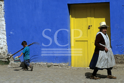 Ollantaytambo, Peru. Woman in traditional dress and boy carrying a fork in front of a blue wall with a yellow door.