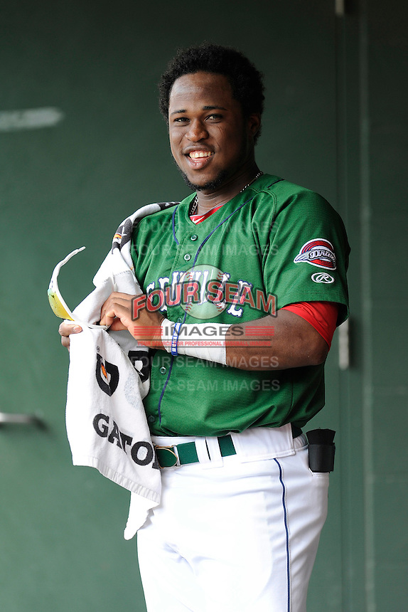 Right fielder Franklin Guzman (10) of the Greenville Drive cleans his sunglasses before a game against the Savannah Sand Gnats on Sunday, August 24, 2014, at Fluor Field at the West End in Greenville, South Carolina. Greenville won, 8-5. (Tom Priddy/Four Seam Images)