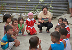 Christian Love Daroy-Gagno, the program director of the Kapatiran-Kaunlaran Foundation (KKFI), plays a game with children in a KKFI-sponsored preschool in Pulilan, a village in Bulacan, Philippines.<br /> <br /> KKFI is supported by United Methodist Women.