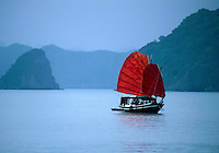 Traditional Vietnamese junk with bright red sails flying, cruises through the misty islands of Halong Bay, Vietnam