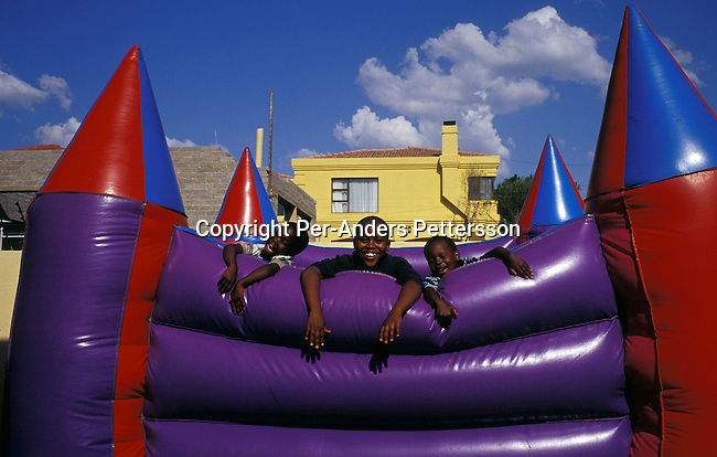 JOHANNESBURG, SOUTH AFRICA -  NOVEMBER 30: Children playing in a jumping castle during  a house warming party on November 30, 2003 in a northern suburb in Johannesburg, South Africa. Malefu Mogorosi, a self-employed woman invited family and friends to the new family house built in Tuscan style. A growing number of people belong to the new black elite in the country. Well educated and connected, they have risen from the poverty in the townships to a very different lifestyle, since the fall of Apartheid and the start of democracy in the country in 1994. .Photo: Per-Anders Pettersson/iAfrika Photos...