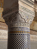 Column covered in zellige tiles and carved marble capital in the Courtyard of the Harem, Glaoui Palace, early 19th century, in Fes, Fes-Boulemane, Northern Morocco. The room has a central fountain, zellige tilework and a carved balcony which is damaged and in need of restoration. Thami Glaoui, Pasha of Marrakech, used this as his Fes residence. The complex consists of 30 fountains, 17 houses, 2 hammams, an oil mill, a mausoleum and cemetery, a madrasa, gardens and stables. Picture by Manuel Cohen