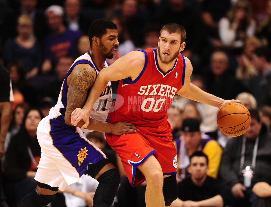 Dec. 28, 2011; Phoenix, AZ, USA; Philadelphia 76ers center Spencer Hawes (right) controls the ball against Phoenix Suns forward Markieff Morris at the US Airways Center. The 76ers defeated the Suns 103-83. Mandatory Credit: Mark J. Rebilas-USA TODAY Sports