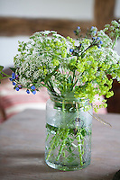 A glass jar in the kitchen displays lady's mantel and other flowers from the garden