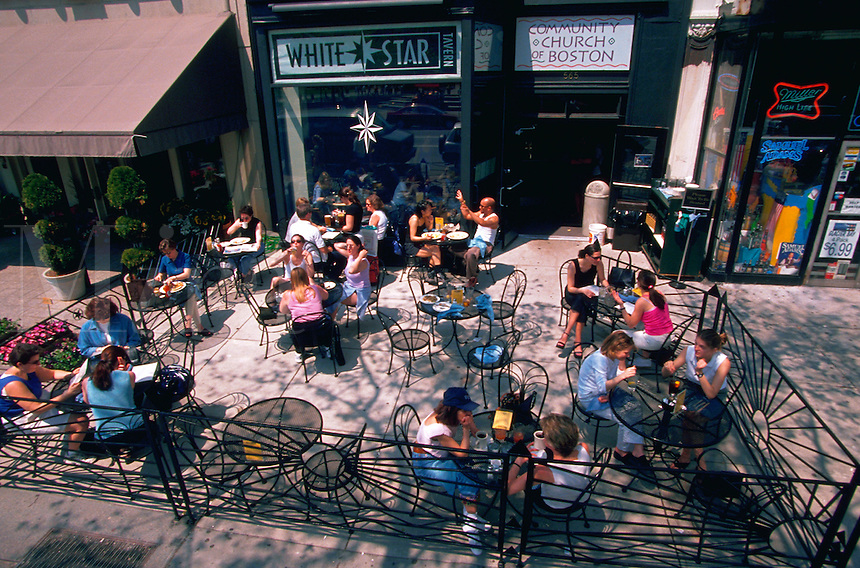 People sitting at outdoor cafe tables on the sidewalk in front of the White Star Tavern on Newbury Street. Boston, Massachusetts.