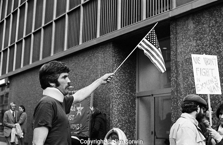 Veteran war protester holding up an American Flag
