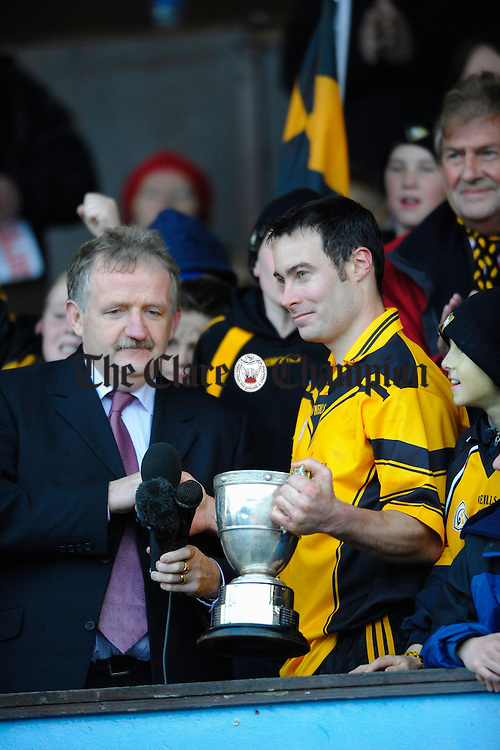 Clonlara captain Paul Collins accepts the cup from Michael O Neill GAA Chairman following their senior county final victory at Cusack Park. Photograph by John Kelly.