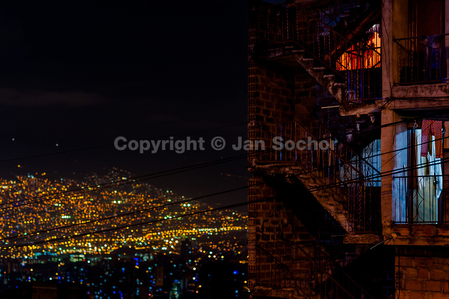 """An unfinished three-story apartment house in the Pablo Escobar neighborhood is seen in the night in front of the city lights of Medellín, Colombia, 29 November 2017. Twenty five years after Pablo Escobar's death, the legacy of the Medellín Cartel leader is alive and flourishing. Although many Colombians who lived through the decades of drug wars, assassinations, kidnappings, reject Pablo Escobar's cult and his celebrity status, there is a significant number of Colombians who admire him, worshipping the questionable """"Robin Hood"""" image he had. Moreover, in the recent years, the popular """"Narcos"""" TV series has inspired thousands of tourists to visit Medellín, creating a booming business for many but causing a controversial rise of narco-tourism."""