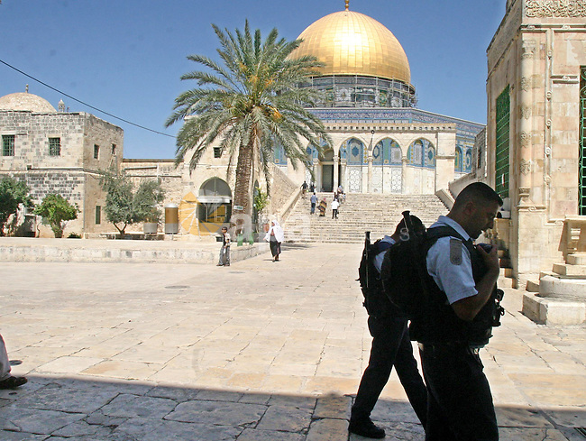 An Israeli Policeman walkes in Al-Aqsa yard in front of the dome of the rock in the old city of Jerusalem on July1,2009. photo by Mahfuz Abu Turk