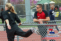 Jefferson City High School hurdles coach Kirk Obermiller visits with his former star pupil, Mizzou senior Leslie Farmer, while she warms up for competition. Farmer, the Missouri Class 4 100-meter hurdles state champion as a senior who also posted top-3 finishes in the 400 and 300 hurdles at that meet, placed 22nd in the 400 hurdles at last year's NCAA DI Outdoor National Championships.