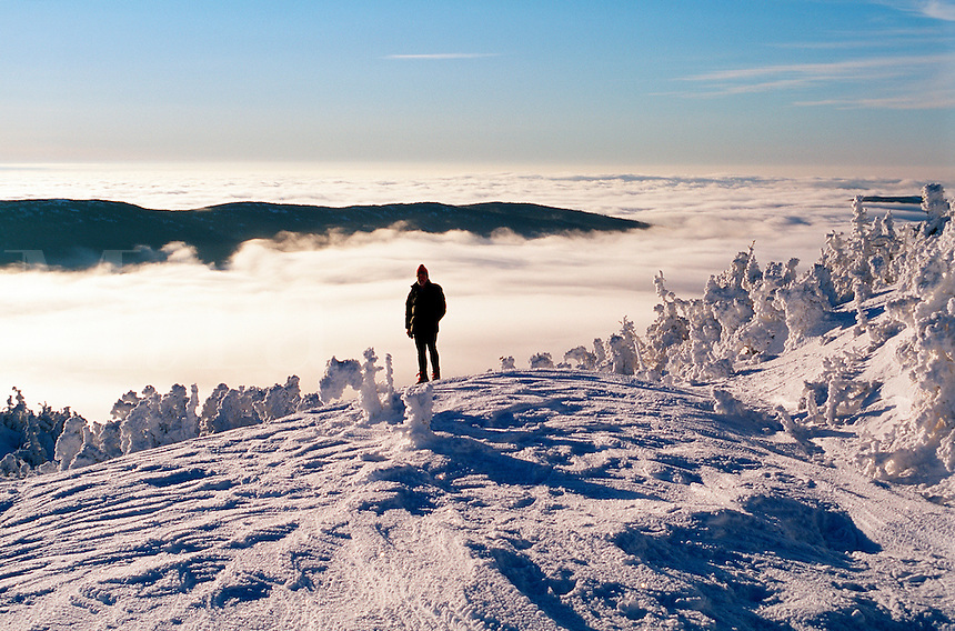 A hiker enjoys a winter sunrise atop Mt. Clinton above a carpet of clouds settled into the valleys of the White Mountain National Park. New Hampshire.