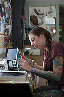 """Artist and illustrator Jada Fitch touches up the paint on one of her """"Home Tweet Home"""" birdhouses in her living room, which doubles as her art studio, in Portland, Maine, USA, on Fri., July 28, 2017. The birdhouses are designed to look like living rooms with small portraits of birds hung on the walls. The birdhouses sell out within minutes on her Etsy store."""
