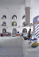 Blue and white wall and floor tiles in stripes and checks in the kitchen perpetuate the coastal theme of the hotel's design