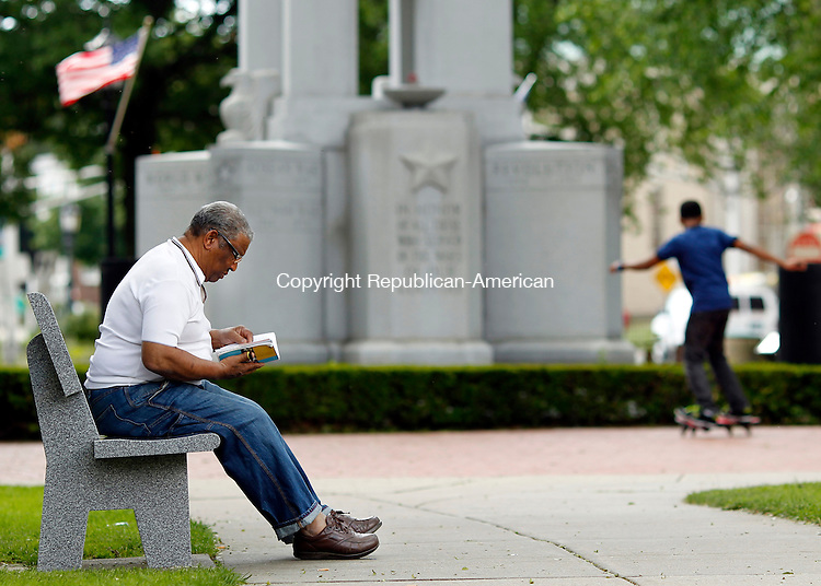 Waterbury, CT-07 June 2012-070712CM02-  Santo Mercedes (left) reads a book as his grandson Rocky Mercedes, 12, both of Waterbury skates around the veterans memorial on the City Green Thursday afternoon in downtown Waterbury.  The City is looking to remodel the Green.    Christopher Massa Republican-American