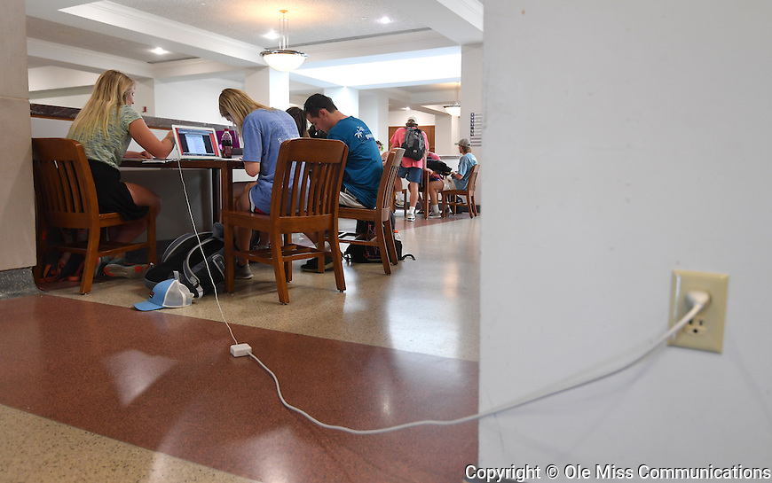 Students laptops, phones and other personal electronics ensure no outlet goes unused when studying for final exams. Photo by Robert Jordan/Ole Miss Communications