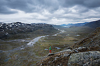 Hiker takes in view over spectacular Alisvaggi from mountain viewpoint near Tjäktja hut, Kungsleden trail, Lapland, Sweden