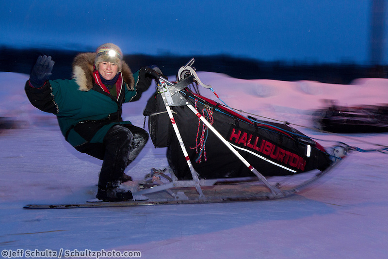 Thursday March, 2012   Jodi Bailey waves to the camera as she leaves the Takotna checkpoint in the early morning after taking her 24 hour layover.  Iditarod 2012.