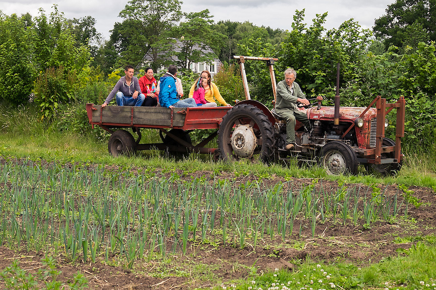 Nederland, Scherpenzeel, 20 juni 2015<br /> Open dag op biologische bedrijven. Lekker naar de Boer.  Door he hele land zijn veel biologische bedrijven open voor publiek. Er zijn informatiestands, rondleidingen, proeverijen. <br /> Boerderij Ruimzicht, biologisch dynamisch tuinbouwbedrijf met boerderijwinkel. Boer geeft rondleiding over de tuinderij. Hij neemt de bezoekers in een laadbak mee achter zijn trekker en maakt een rondje over het land.<br /> <br /> Foto: Michiel Wijnbergh