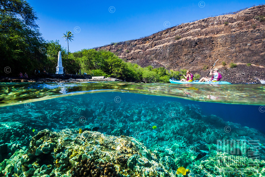 A couple kayaking by the Captain Cook Monument, Kealakekua Bay, with camera half below water showing reef and fish, Big Island