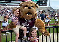 Young MSU fans smiling with Bully mascot during Maroon and White football game.<br />  (photo by Lizzy Powers / &copy; Mississippi State University)