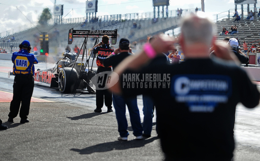 Jan 24, 2009; Chandler, AZ, USA; Crew members look on as NHRA top fuel dragster driver Cory McClenathan launches off the starting line during testing at the National Time Trials at Firebird International Raceway. Mandatory Credit: Mark J. Rebilas-