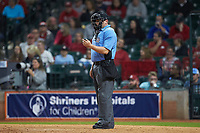 Home plate umpire Clint Fagan checks his indicator during the NCAA baseball game between the Baylor Bears an the Arkansas Razorbacks in game nine of the 2020 Shriners Hospitals for Children College Classic at Minute Maid Park on March 1, 2020 in Houston, Texas. The Bears defeated the Razorbacks 3-2. (Brian Westerholt/Four Seam Images)