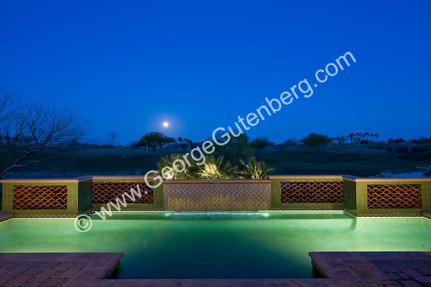 Night time view of swimming pool waterfeature with moon in background