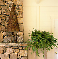 One of a pair of ornamental trees sculpted in metal on the fieldstone chimney piece in the dining room