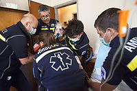 Switzerland. Canton Ticino. Mezzovico. A senior man is carried seated on a chair, then by ambulance to the hospital for medical examinations. The elderly man is suffering from severe respiratory problems. The emergency doctor Daniele Speciale (with beard and glasses) is working with four paramedics. They all work for the Croce Verde Lugano. They wear blue uniforms, medical gloves and surgical masks. The man (C) and the woman (C) are professional certified nurses, both men (L) (R) are volunteers specifically trained in emergency rescue. The senior citizen has a mask on his face and receives oxygen from a medical ventilator carried by the doctor. A medical ventilator (or simply ventilator in context) is a mechanical ventilator, a machine designed to move breathable air into and out of the lungs, to provide breathing for a patient who is physically unable to breathe, or breathing insufficiently. The Croce Verde Lugano is a private organization which ensure health safety by addressing different emergencies services and rescue services. Volunteering is generally considered an altruistic activity where an individual provides services for no financial or social gain to benefit another person, group or organization. Volunteering is also renowned for skill development and is often intended to promote goodness or to improve human quality of life. Medical gloves are made of different polymers including latex, nitrile rubber, polyvinyl chloride and neoprene. 14.01.2018 © 2018 Didier Ruef