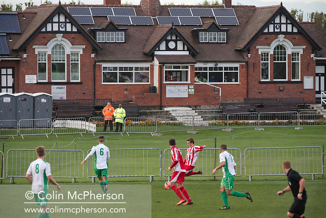Home supporters watching the action during the first half of Stourbridge FC's match against visitors Biggleswade Town FC (green shirts) at the War memorial Athletic Ground in the FA Cup first round, a stadium which also doubles as a cricket ground. The match was won by the home side by four goals to one, watched by a capacity crowd of 1605. It was Biggleswade's first appearance at the first round stage of the cup, winners Stourbridge went on to play Stevenage in the second round.
