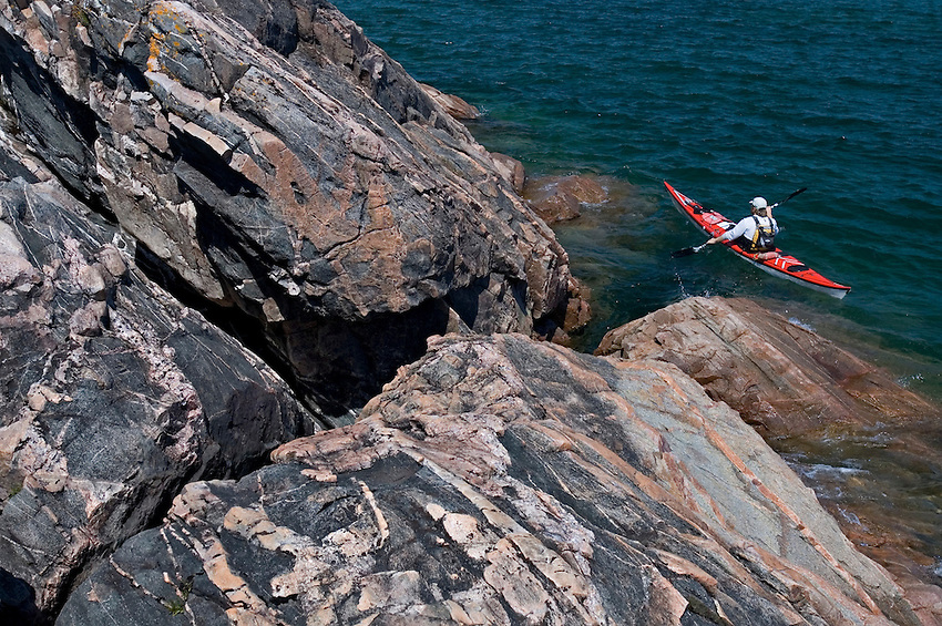 A sea kayaker explores Granite Point on Lake Superior between Big Bay and Marquette Michigan.