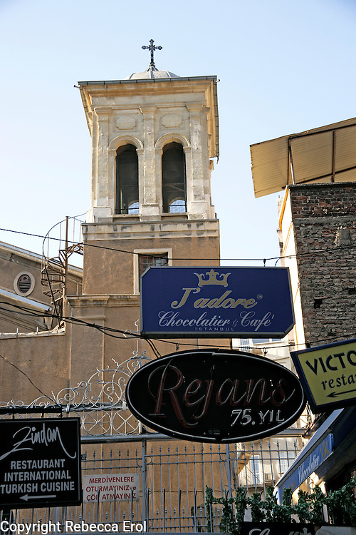 Greek Orthodox Church off Istiklal Street with advertising for restaurants littering its entrance, Beyoglu, Istanbul, Turkey