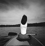 Negative file #98-085-K-9. Woman removing sweater in bow of canoe. Moosehead Lake, MA. 1/2