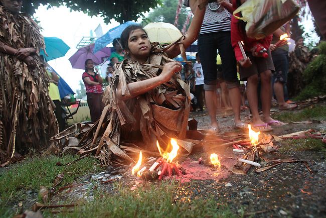 "A steady monsoon rain pours down, as a young woman listens to Mass during the annual Taong Putik, or ""mud people,"" festival in Bibiclat, on Luzon island, Philippines. The festival honors St. John the Baptist, and devotees cover themselves in mud, banana leaves and vines to symbolize the animal skins he wore in the Bible. June 24, 2011."