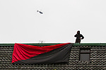 """© Joel Goodman - 07973 332324 . 26/03/2011 . London , UK . A protester suspends a black and red anarcho-syndiclist flag from an occupied rooftop . Hundreds of thousands of people attending an anti cuts demonstration under the banner """" March for the Alternative """" in central London , in protest at the coalition government's austerity measures . Photo credit : Joel Goodman"""