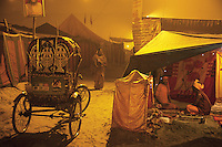 India. Uttar Pradesh state. Allahabad. Maha Kumbh Mela. Two men seated at night outside their tent. A woman wearing a saree and a bicycle rickshaw. Cycle rickshaws are human-powered, a type of tricycle designed to carry passengers in addition to the driver. The Kumbh Mela, believed to be the largest religious gathering is held every 12 years on the banks of the 'Sangam'- the confluence of the holy rivers Ganga, Yamuna and the mythical Saraswati. The Maha (great) Kumbh Mela, which comes after 12 Purna Kumbh Mela, or 144 years, is always held at Allahabad. Uttar Pradesh (abbreviated U.P.) is a state located in northern India. 11.02.13 © 2013 Didier Ruef