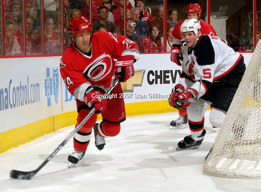 Carolina Hurricanes' Scott Walker carries the puck behind the net defended by the New Jersey Devils' Colin White Thursday, March 15, 2007 at the RBC Center in Raleigh, NC. New Jersey won 3-2.