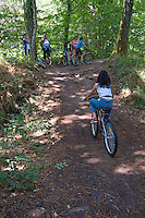 Girl catching up to family mountain biking in Landes Forest, Hostens, Aquitaine, France.