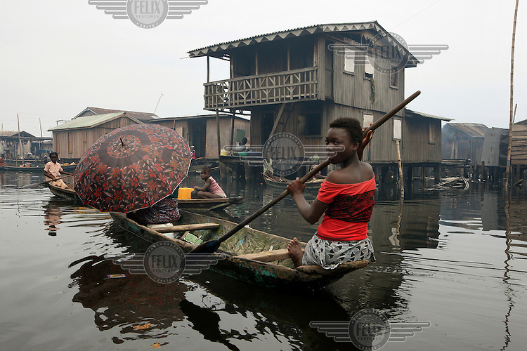 A young girl paddles a canoe past a house in Makoko, a slum district on Lagos Lagoon.