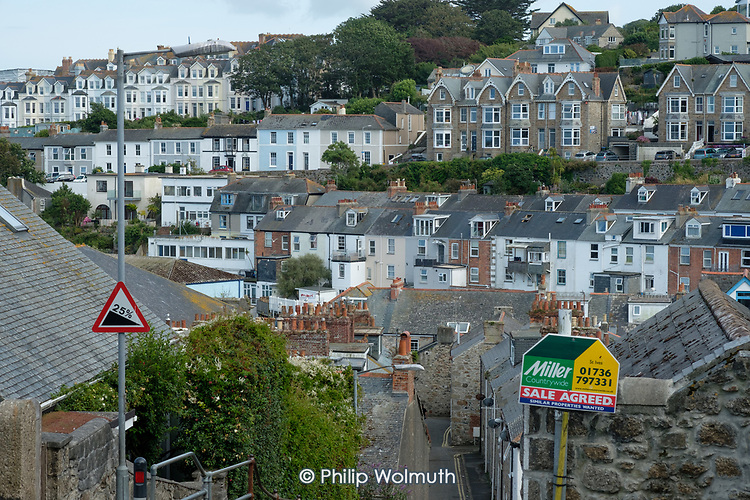 Housing on a steep hillside and estate agent board, St.Ives, Cornwall.