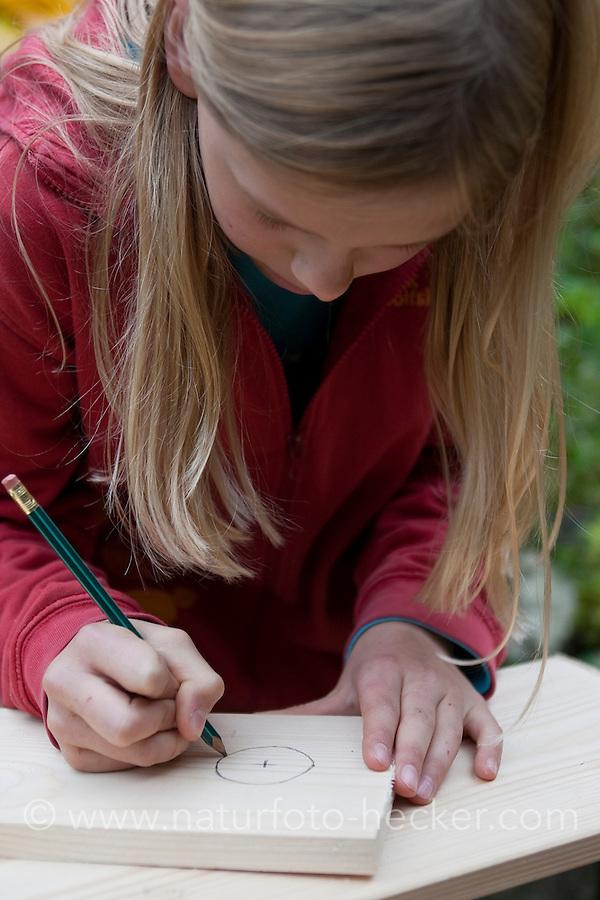 Mädchen baut einen Vogel-Nistkasten aus Brettern, 3. Schritt: Einflugloch auf Vorderseite aufzeichnen
