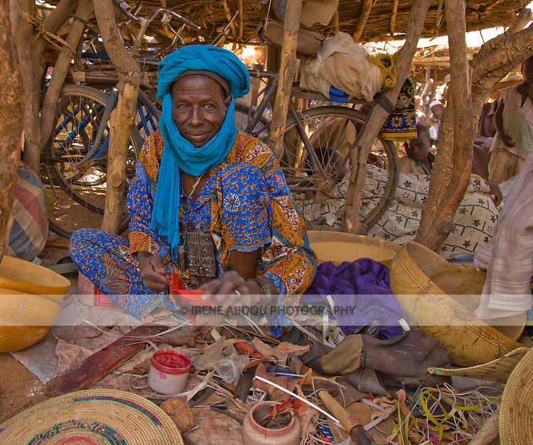 In Niger, a Bouzou leather worker sits in a market stall in the town of Torodi's weekly market, crafting leather shoes that he sells to the marketgoers.