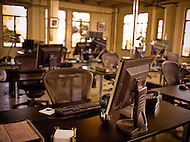 An office is filled with desks and computer with bright open windows in the back