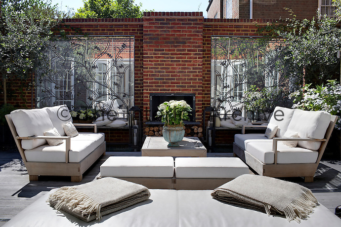 The central courtyard is furnished with comfortable sofas and a fireplace in an external brick wall flanked by mirrored alcoves with decorative wrought-iron screens